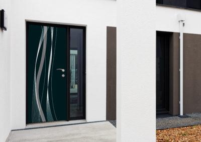 Porte d'entrée modèle Arwen gris clair sur la Villa E-Roise - Ouvrant Solobloc avec encadrement alu au coloris noir, habillé d'une poignée Antalia