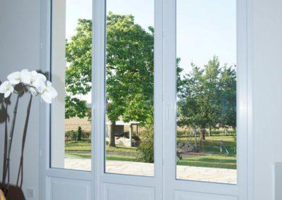 Porte fenêtre en PVC blanc avec soubassement et coffre intérieur de volet roulant