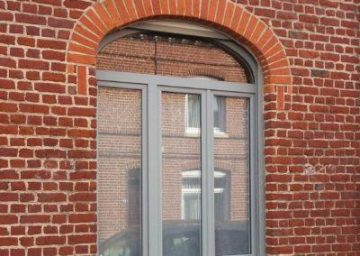 Menuiserie à 3 vantaux sous imposte vitrée cintrée en PVC laqué gris RAL 7040